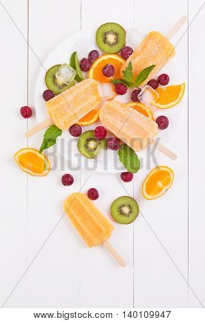Homemade orange popsicles on a plate with mint kiwi frozen cherry and orange slices on a white wooden background. Top view with copyspace