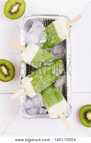 Frosty popsicles of kiwi in a box on a white wooden background