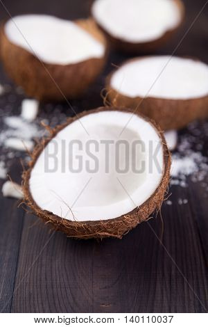 Coconut halves with shell on a dark wooden background