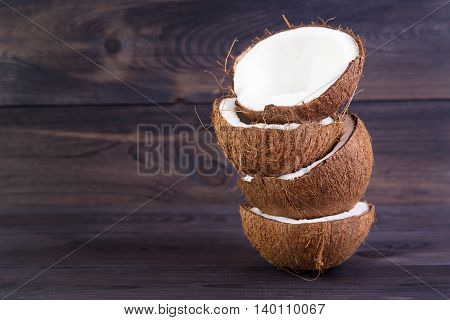 Tropical coconut halves with shell on a dark wooden background
