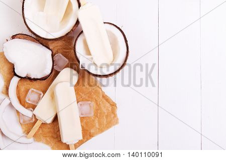 Homemade frosty coconut popsicles on a paper with ice on a white wooden background
