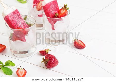 Homemade frosty strawberry popsicles in a glass with mint on a white wooden table