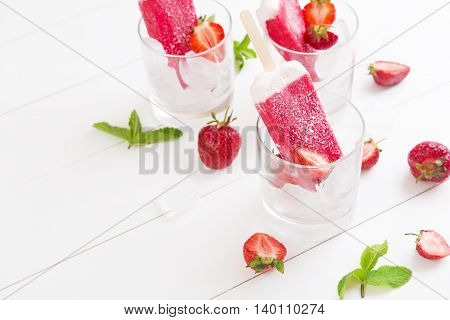 Homemade strawberry popsicles in a glass with mint on a white wooden table