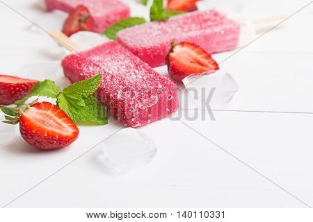 Homemade frosty strawberry popsicle wiht mint and ice on a white wooden background