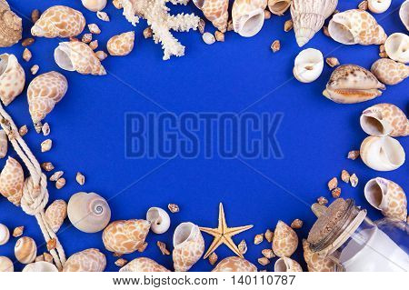 Colorful marine items - seashells starfish coral bottle with note and rope arranged as frame. Top view with copyspace