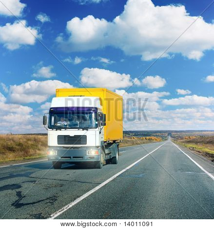 Truck on asphalt road under blue sky with clouds