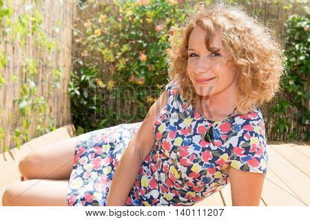 Portrait Of A Beautiful Young Woman Sitting By Swimming Pool