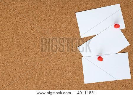 Cork Board With Three White Cards Pinned To It