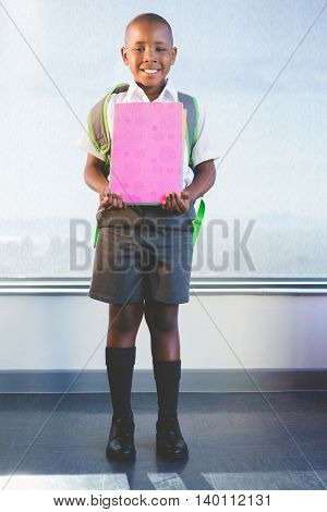 Happy schoolkid holding books and standing in classroom at school