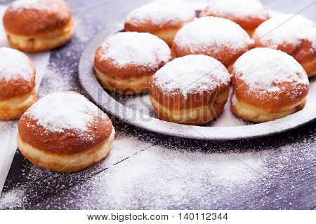 German donuts - berliner with jam and icing sugar in a tray on a dark wooden background. Space for text