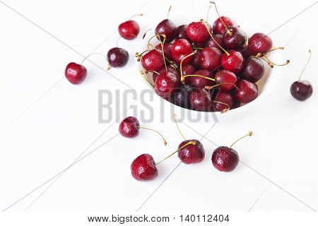 Red cherries with water drops in bowl on a white background. Space for text