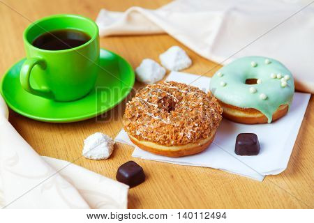 Delicious donuts and cup of black coffee morning sweet breakfast