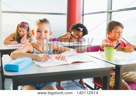 Schoolkids doing homework in classroom at school