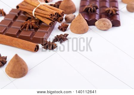 Broken chocolate bar with candy truffles cinnamon and anise on a white wooden background
