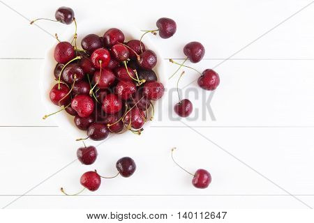 Ripe red cherries with water drops in bowl on a white background. Top view with copyspace