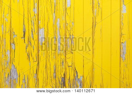 Vertical background of the old wooden planks with cracked yellow paint