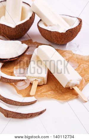 Homemade coconut popsicles on a paper with ice on a white wooden background. Space for text