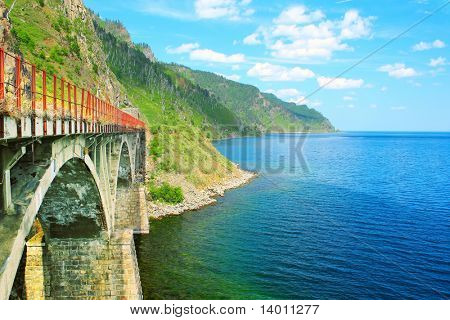 Old bridge between lake with blue clear water and mountains
