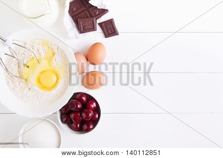 Ingredients for the pie - cherry flour eggs sugar milk and chocolate on a white wooden bachground