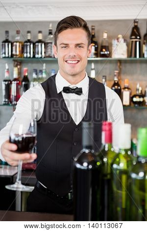 Portrait of waiter holding a glass of wine in restaurant