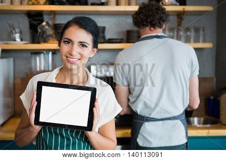 Portrait of waitress holding digital tablet while waiter working in background