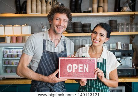 Portrait of waiter and waitress holding open signboard in cafeteria
