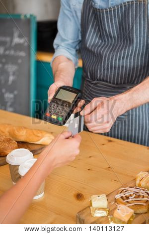 Close-up of woman making payment through credit card in cafeteria