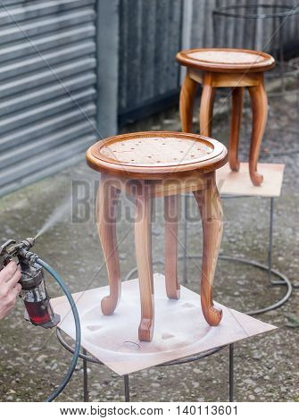 Carpenter is covering stool by lacquer. Furniture varnishing using sprayer or pulverizer