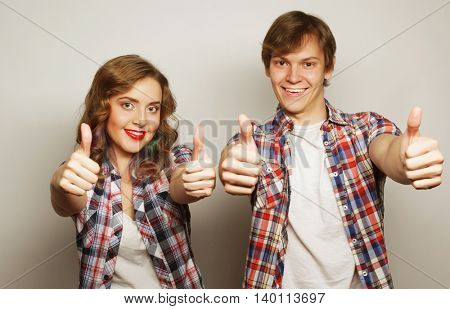 people, friendship, love and leisure concept - lovely couple with thumbs-up gesture isolated on white