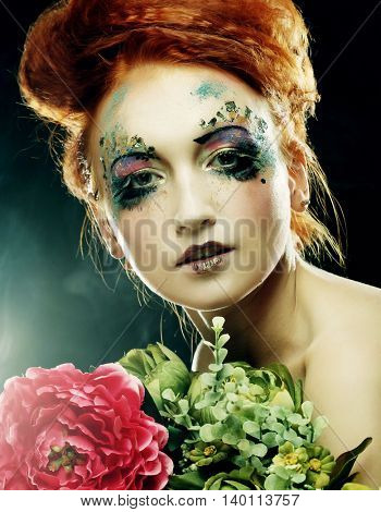 Young beautiful redhair woman with bright creative visage holding flowers