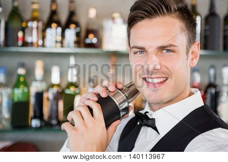 Portrait of waiter shaking cocktail at bar counter in restaurant