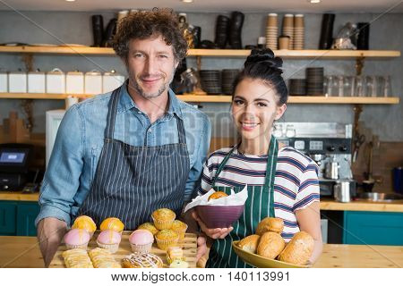 Portrait of waiter and waitress holding wooden tray and bowl with snacks and dessert in cafeteria