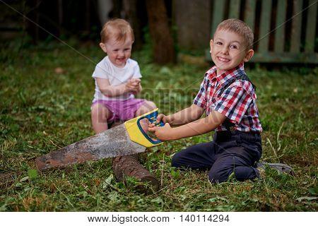 little boy sawing fallen tree in garden