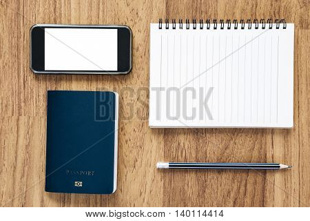 Blank notebook and mobile phone with blue passport on wooden desk, travel concepts