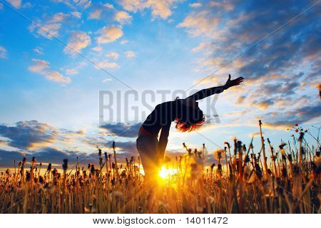 Young woman under sunset light in meadow with herbs