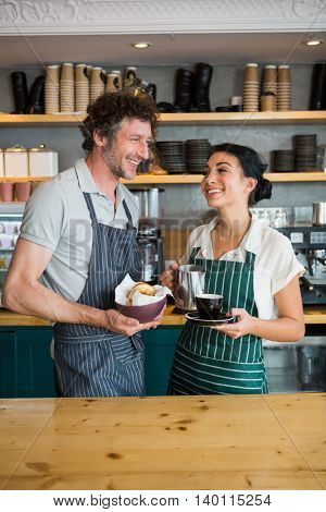 Waiter and waitress holding bowl with snack and coffee cup in cafeteria