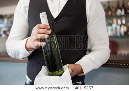 Mid section of waiter holding a bottle of wine in restaurant