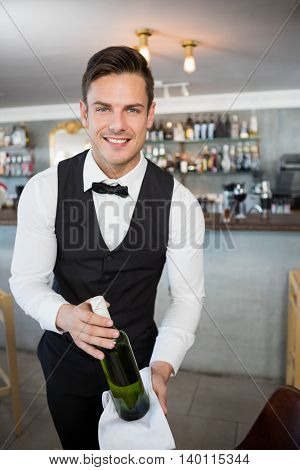 Portrait of waiter holding a bottle of wine in restaurant