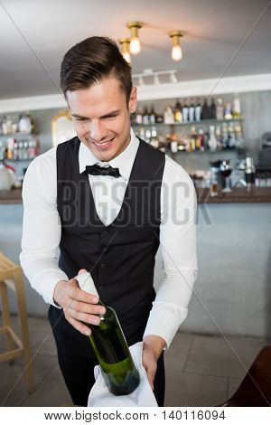 Waiter holding a bottle of wine in restaurant