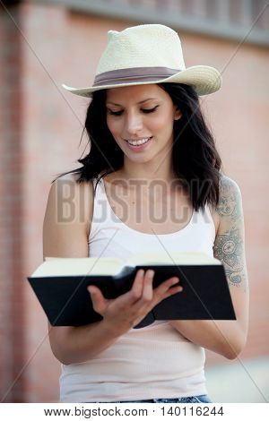 Brunette pretty woman reading a book at street