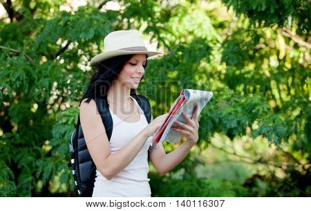 Brunette woman with straw hat walking through the woods while referring to a map
