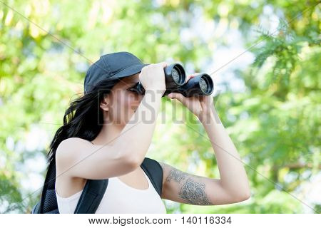 Beautiful woman with cap and backpack looking through binoculars while hiking trip