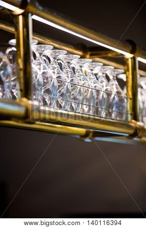 Wine glass arranged in bar rack at bar