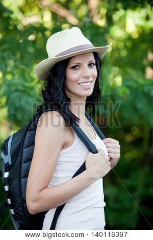 Brunette woman with straw hat walking through the woods