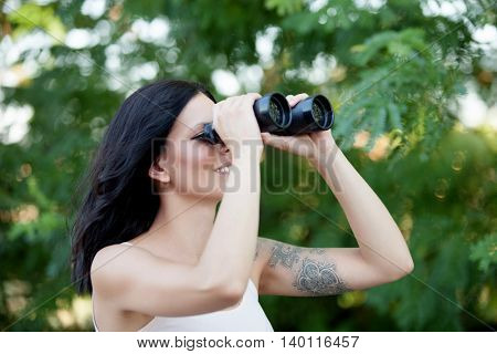 Brunette woman looking through the binoculars while strolling through a lush forest