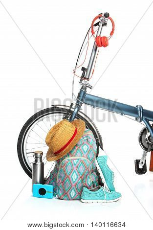 The new modern urban folding bike and suitcase, sneakers, thermos, hat on white background. The travel, tourism and holidays concept