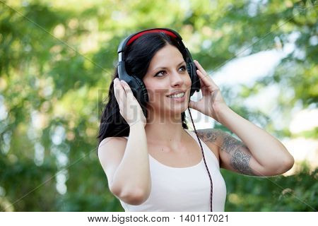 Brunette girl with headphones walking on a park