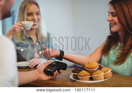 Happy female customer with smart watch paying at cafe