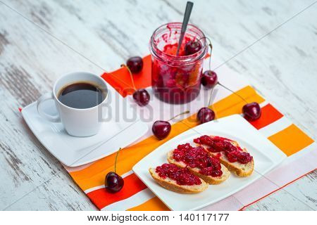 Sandwiches with cherry jam and coffee for breakfast