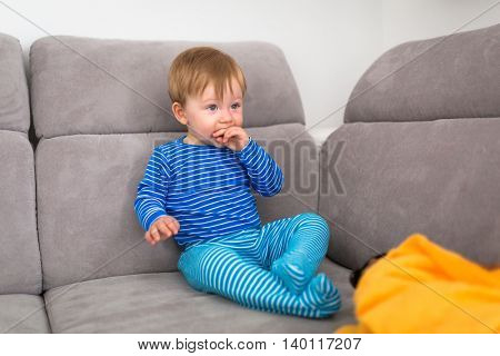Baby boy sitting on the couch and watch tv